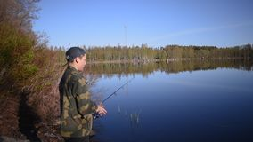 Ο ψαράς, νεαρός άνδρας, ρίχνει έναν εξοπλισμό αλιείας στη λίμνη απόθεμα βίντεο