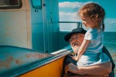 Ο ψαράς παππούδων παρουσιάζει στην εγγονή βάρκα του Στοκ εικόνες με δικαίωμα ελεύθερης χρήσης
