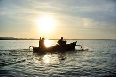 Ο ψαράς πηγαίνει τη σκιαγραφία στο ηλιοβασίλεμα/την ανατολή Στοκ εικόνες με δικαίωμα ελεύθερης χρήσης