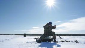 Ο ψαράς πιάνει ένα ψάρι, χειμερινός αθλητισμός, χειμερινό χόμπι απόθεμα βίντεο