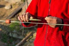 Ο ψαράς πλέκει τα δίχτυα του ψαρέματος Στοκ Εικόνες