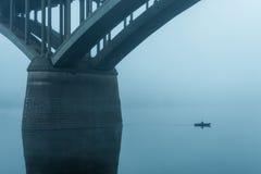 Ο ψαράς σε μια μικρή βάρκα πλέει δίπλα στους στυλοβάτες της γέφυρας στην ομίχλη Στοκ φωτογραφίες με δικαίωμα ελεύθερης χρήσης