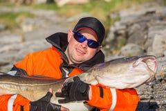 Ο ψαράς στα γυαλιά ηλίου κρατά ένα μεγάλο ψάρι Στοκ Φωτογραφίες