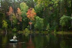 Ο ψαράς στη βάρκα είναι στη δασική λίμνη το φθινόπωρο Στοκ Φωτογραφίες