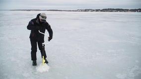 Ο ψαράς τρυπά μια τρύπα σε έναν παγωμένο ποταμό με τρυπάνι απόθεμα βίντεο