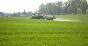 Ο ψεκασμός τρακτέρ λιπαίνει στον τομέα με τις χημικές ουσίες στον τομέα γεωργίας απόθεμα βίντεο