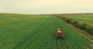 _ Ο ψεκασμός τρακτέρ λιπαίνει τον τομέα με τις χημικές ουσίες ζιζανιοκτόνου εντομοκτόνου στον τομέα γεωργίας απόθεμα βίντεο