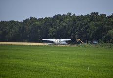 Ο ψεκασμός των λιπασμάτων και των φυτοφαρμάκων στον τομέα με τα αεροσκάφη Στοκ Φωτογραφίες