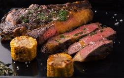 Ο ψημένος στη σχάρα μαύρος Angus Steak Ribeye με το δεντρολίβανο και το καλαμπόκι Στοκ Φωτογραφία