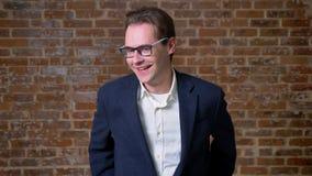 Ο ψυχρός καυκάσιος επιχειρηματίας γελά δίπλα στη κάμερα στην κίνηση που στέκεται στην ίδια θέση, υπόβαθρο τούβλου φιλμ μικρού μήκους