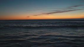 Ο ωκεανός είναι βαθιά μπλε, τα κύματα πλένονται από την αμμώδη παραλία της θερινής ακτής, οι ακτίνες του ήλιου απόθεμα βίντεο