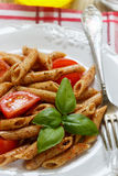 Ολόκληρα ζυμαρικά σίτου με τις ντομάτες, βασιλικός, ελαιόλαδο, καρυκεύματα Στοκ εικόνα με δικαίωμα ελεύθερης χρήσης