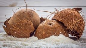 Ολόκληρα διεσπαρμένα καρύδια ξέσματα καρύδων στο ξύλινο υπόβαθρο Στοκ φωτογραφία με δικαίωμα ελεύθερης χρήσης