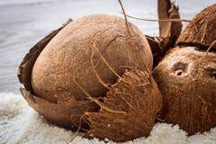 Ολόκληρα διεσπαρμένα καρύδια ξέσματα καρύδων στο ξύλινο υπόβαθρο Στοκ φωτογραφίες με δικαίωμα ελεύθερης χρήσης