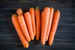 Ολόκληρα καρότα στο σκοτεινό ξύλινο πίνακα Στοκ Εικόνα