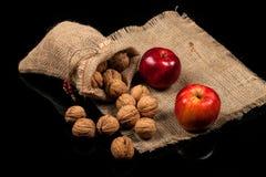Ολόκληρα καρύδια και μήλα σε έναν πίνακα σε ένα μαύρο υπόβαθρο Στοκ Εικόνα