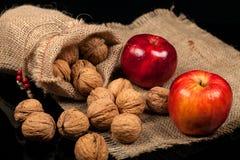 Ολόκληρα καρύδια και μήλα σε έναν πίνακα σε ένα μαύρο υπόβαθρο Στοκ Φωτογραφία