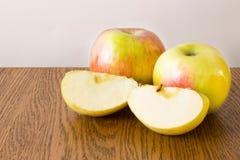 Ολόκληρα μήλο δύο και τέταρτα που βρίσκονται σε έναν ξύλινο Στοκ φωτογραφίες με δικαίωμα ελεύθερης χρήσης