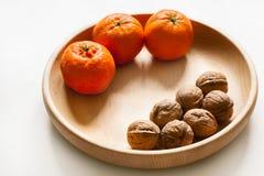 Ολόκληρα ξύλα καρυδιάς στο ξύλινο κύπελλο με την πορτοκαλιά έννοια διατροφής φρούτων υγιή Στοκ Εικόνα