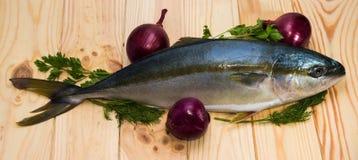 Ολόκληρα στρογγυλά yellowtail ψαριών και τρία κόκκινα κρεμμύδια Στοκ Εικόνες