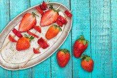 Ολόκληρες φρέσκες κόκκινες φράουλες και τεμαχισμένες φράουλες στα ξύλινα οβελίδια στο εκλεκτής ποιότητας πιάτο ξύλινο tabletop Στοκ φωτογραφία με δικαίωμα ελεύθερης χρήσης