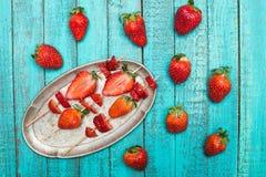 Ολόκληρες φρέσκες κόκκινες φράουλες και τεμαχισμένες φράουλες στα ξύλινα οβελίδια στο εκλεκτής ποιότητας πιάτο ξύλινο tabletop Στοκ Εικόνα