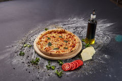 Ολόκληρη ιταλική εύγευστη φρέσκια πίτσα με την ντομάτα και pepperoni σε ένα σκοτεινό υπόβαθρο Πίτσα στο μαύρο πίνακα με τα συστατ Στοκ εικόνες με δικαίωμα ελεύθερης χρήσης