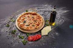Ολόκληρη ιταλική εύγευστη φρέσκια πίτσα με την ντομάτα και pepperoni σε ένα σκοτεινό υπόβαθρο Πίτσα στο μαύρο πίνακα με τα συστατ Στοκ Φωτογραφίες