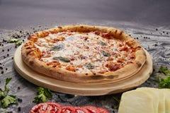 Ολόκληρη ιταλική εύγευστη φρέσκια πίτσα με την ντομάτα και pepperoni σε ένα σκοτεινό υπόβαθρο Πίτσα στο μαύρο πίνακα με τα συστατ Στοκ Εικόνες