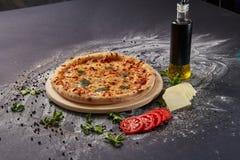 Ολόκληρη ιταλική εύγευστη φρέσκια πίτσα με την ντομάτα και pepperoni σε ένα σκοτεινό υπόβαθρο Πίτσα στο μαύρο πίνακα με τα συστατ Στοκ φωτογραφία με δικαίωμα ελεύθερης χρήσης