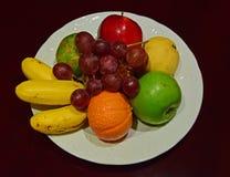 Ολόκληρη πιατέλα φρούτων στο άσπρο πιάτο στον ξύλινο πίνακα στοκ εικόνες