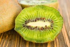 Ολόκληροι τροφίμων σπόροι μισών ακτινίδιων φρούτων πράσινοι που κόβουν τον πίνακα Στοκ εικόνες με δικαίωμα ελεύθερης χρήσης