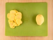 Ολόκληρος και τεμαχισμένος potatoe στον πράσινο χρησιμοποιημένο πίνακα Στοκ φωτογραφία με δικαίωμα ελεύθερης χρήσης