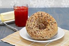 Ολόκληρο σιτάρι, πολυ σπαρμένα bagels με μια πλευρά του βουτύρου και του αχύρου Στοκ Εικόνα