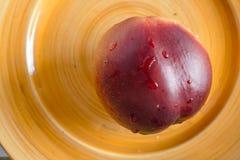 Ολόκληρο το κόκκινος-πορτοκαλί ροδάκινο σε ένα κίτρινο πιάτο Στοκ εικόνες με δικαίωμα ελεύθερης χρήσης