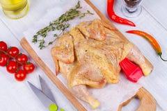 Ολόκληρο το φρέσκο ακατέργαστο κοτόπουλο προετοιμάστηκε για το ψητό με το θυμάρι, το βασιλικό και το κεράσι ντοματών Στοκ Εικόνες