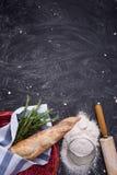 Ολόκληρο baguette σίτου στο κόκκινο καλάθι με το δεντρολίβανο, το αλεύρι και την κυλώντας καρφίτσα πέρα από το μαύρο υπόβαθρο gru Στοκ φωτογραφίες με δικαίωμα ελεύθερης χρήσης