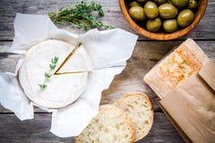 Ολόκληρο Camembert τυρί με το θυμάρι, τις ελιές και το baguette Στοκ Φωτογραφίες
