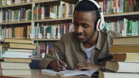 Ο όμορφος άνδρας σπουδαστής αφροαμερικάνων που φορά τα ακουστικά ακούει τη συνεδρίαση μουσικής στον πίνακα στη μεγάλη ευρύχωρη βι απόθεμα βίντεο