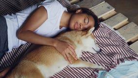 Ο όμορφος έφηβος αφροαμερικάνων και το λατρευτό σκυλί κατοικίδιων ζώων κοιμούνται μαζί στο ξύλινο κρεβάτι, το κορίτσι φορά απόθεμα βίντεο