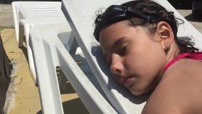 Ο όμορφος έφηβος νέων κοριτσιών στο μαγιό βρίσκεται στο μόνιππο -μόνιππο-longue κοντά στην πισίνα και τον ύπνο απόθεμα βίντεο