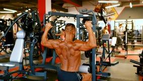 Ο όμορφος αθλητής ασκεί στο κέντρο γυμναστικής Σκληροί μυ'ες κατάρτισης ατόμων Bodybuilder στη μηχανή κατάρτισης φιλμ μικρού μήκους