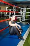 Ο όμορφος αθλητής κοριτσιών κάθεται στο εγκιβωτίζοντας δαχτυλίδι στη γυμναστική στοκ φωτογραφία