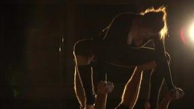 Ο όμορφος ακροβάτης γυναικών κάθεται στα πόδια ενός άνδρα, σε αργή κίνηση απόθεμα βίντεο