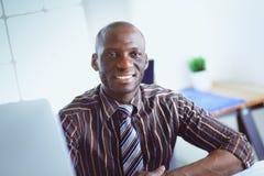 Ο όμορφος αμερικανικός επιχειρηματίας Afro στο κλασικό κοστούμι χρησιμοποιεί ένα lap-top και χαμογελά εργαζόμενος στην αρχή Στοκ Εικόνες