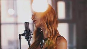 Ο όμορφος αοιδός τζαζ με φωτεινό αποτελεί να αποδώσει στη σκηνή στο μικρόφωνο συναυλίας απόθεμα βίντεο
