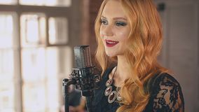 Ο όμορφος αοιδός τζαζ με φωτεινό αποτελεί να τραγουδήσει στη σκηνή στο μικρόφωνο συναυλίας απόθεμα βίντεο