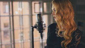 Ο όμορφος αοιδός τζαζ στην κόκκινη φούστα με φωτεινό αποτελεί στη σκηνή στο μικρόφωνο φιλμ μικρού μήκους
