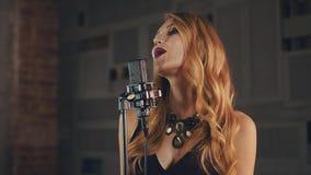 Ο όμορφος αοιδός τζαζ στο φόρεμα αποδίδει στη σκηνή στο μικρόφωνο Σκοτεινός αποτελέστε απόθεμα βίντεο