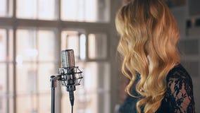 Ο όμορφος αοιδός τζαζ στο φόρεμα με φωτεινό αποτελεί στη σκηνή στο μικρόφωνο συναυλίας απόθεμα βίντεο